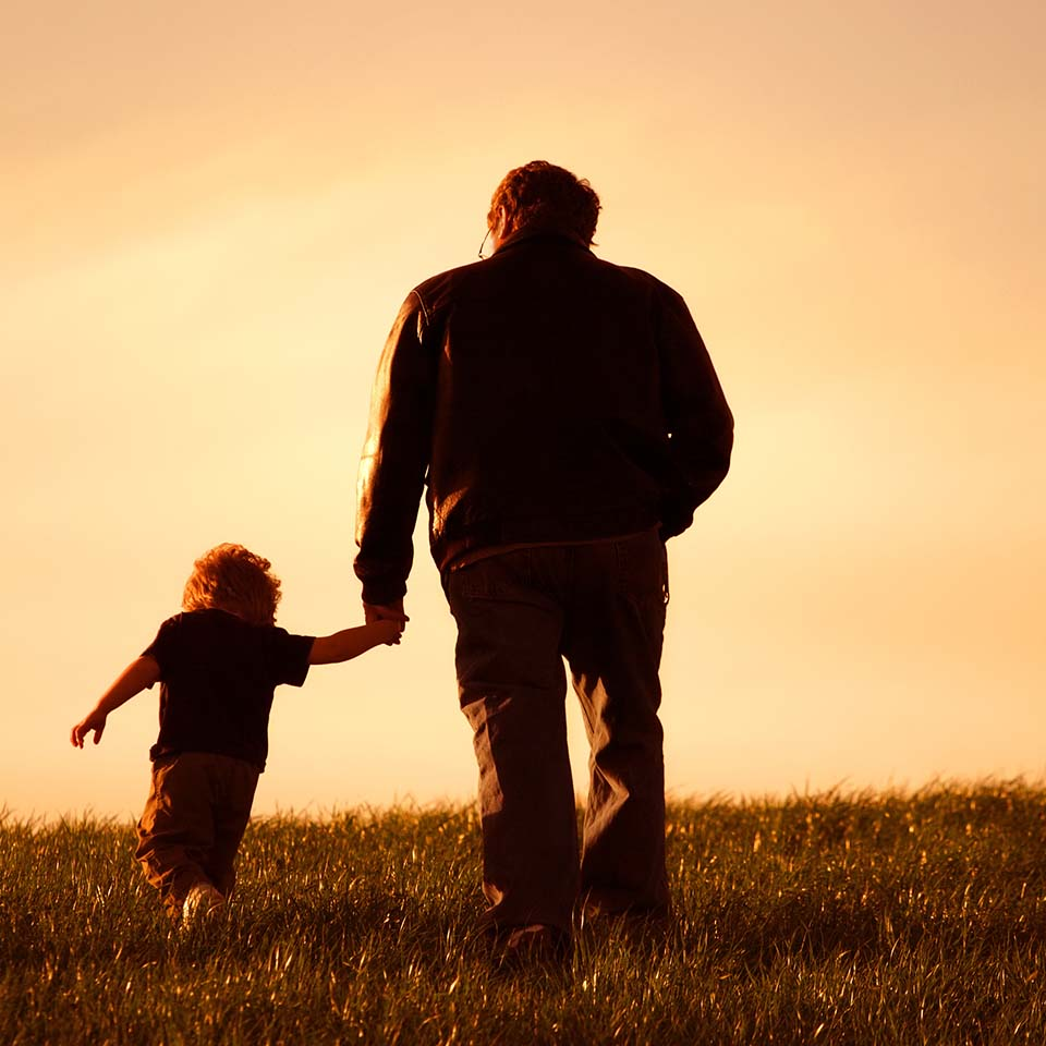 Father and son silhouette walking across field at sunset