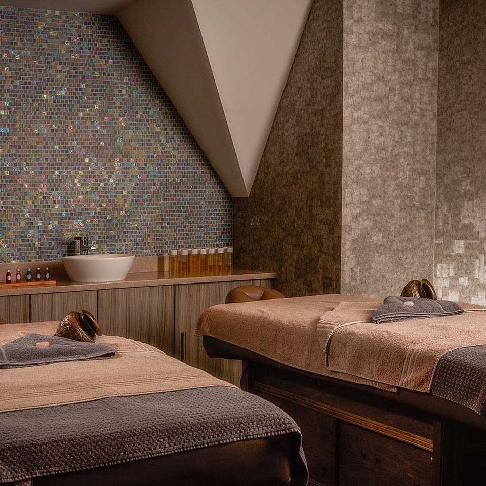 Treatment room at Mallory Court Elan Spa, double treatment beds with moroccon bowls on bed